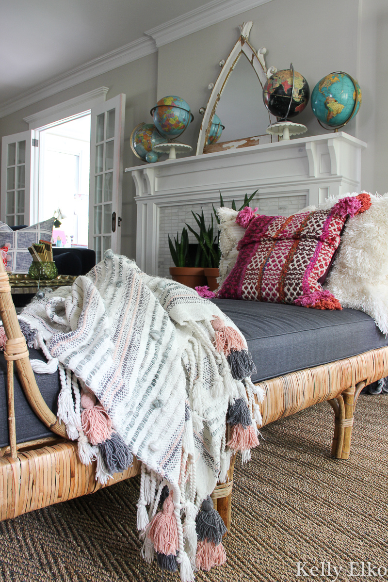 Love this eclectic boho living room with rattan daybed and vintage globe collection on the mantel kellyelko.com #eclecticdecor #livingroomdecor #manteldecor #vintagemodern #vintagedecor #rattan #rattanfurniture #daybed #collections #collect #manteldecor #mantel #interiordesign #cozydecor #globes #kellyelko #article