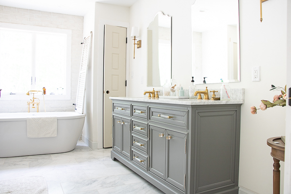 Beautiful master bathroom with double vanity, freestanding tub and brass fixtures #masterbath #bathroom #neutralbathroom #farmhouse #farmhousebathroom #vintagemodern #brass