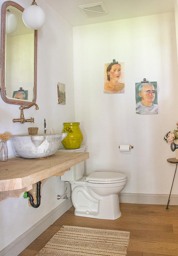 Beautiful powder room with reclaimed wood vanity and vintage Hamam #hamam #powderroom #farmhousedecor #vintagemodern #portraits #portraitpaintings #reclaimedwood #farmhousedecor