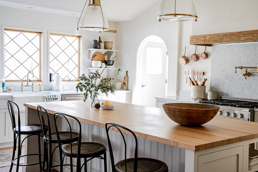 European farmhouse kitchen with a mix of marble and butcher block counters and brass accents and lighting #farmhouse #farmhousekitchen #kitchen #whitekitchen #butcherblockcounter #kitchendecor #kitchenreno #kitchenlighting #barstools