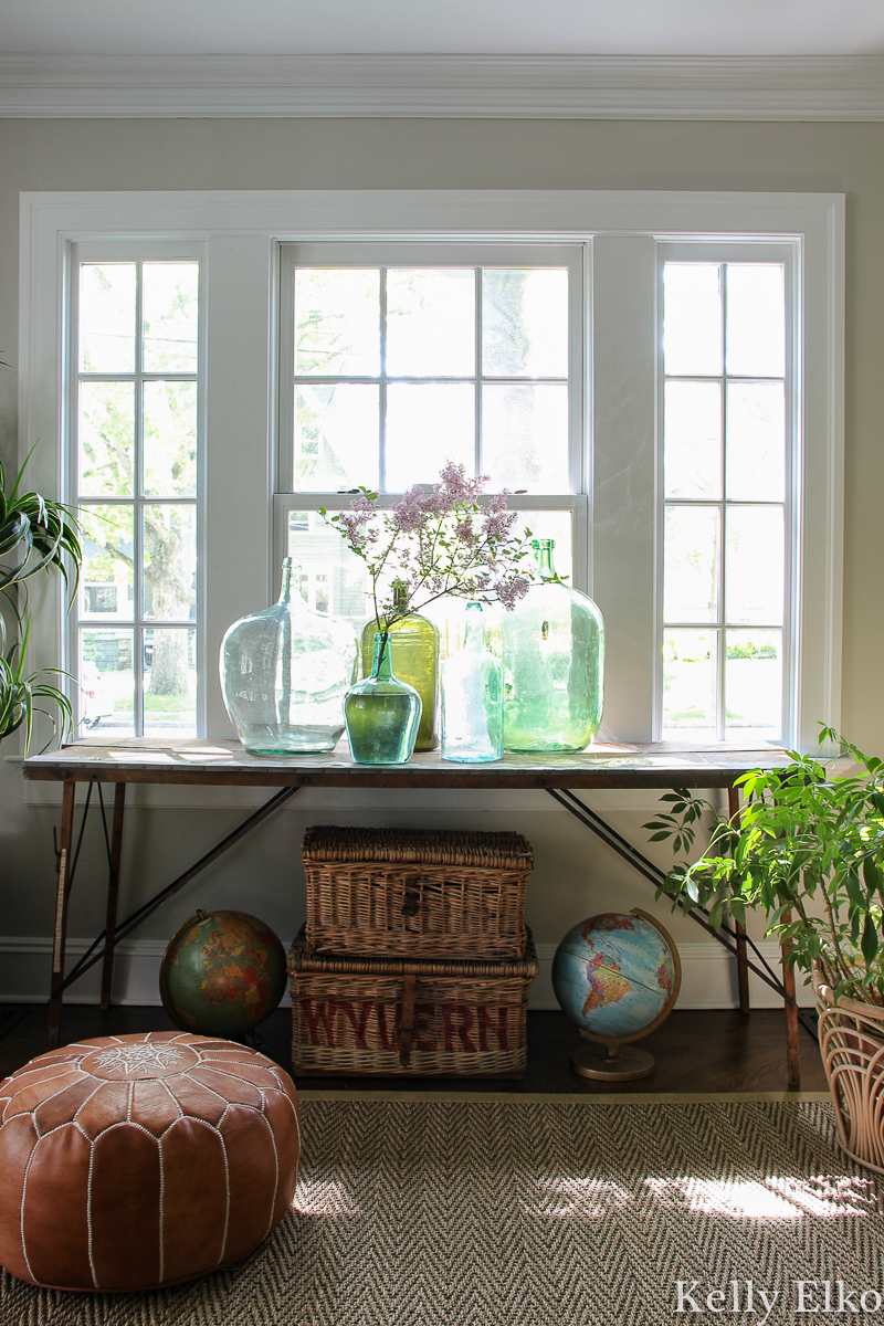 Beautiful antique wallpaper pasting table with a collection of vintage glass demijohns kellyelko.com #antiques #antiquedecor #vintagedecor #eclecticdecor #demijohn #collections #collect #vintagemodern #bohodecor #plants #houseplants #interiorstyling #kellyelko