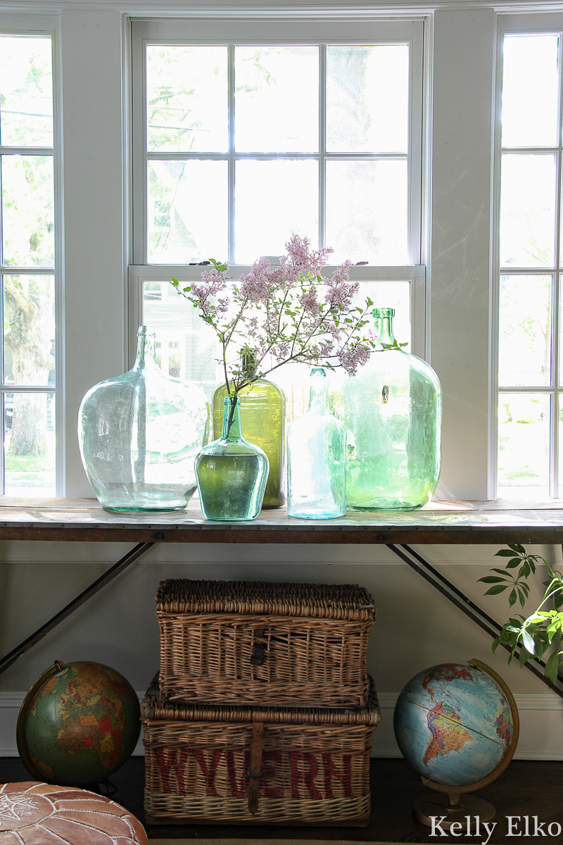 Beautiful antique wallpaper pasting table with a collection of vintage glass demijohns kellyelko.com #antiques #antiquedecor #vintagedecor #eclecticdecor #demijohn #collections #collect #vintagemodern #bohodecor #plants #houseplants #interiorstyling #kellyelko #wicker