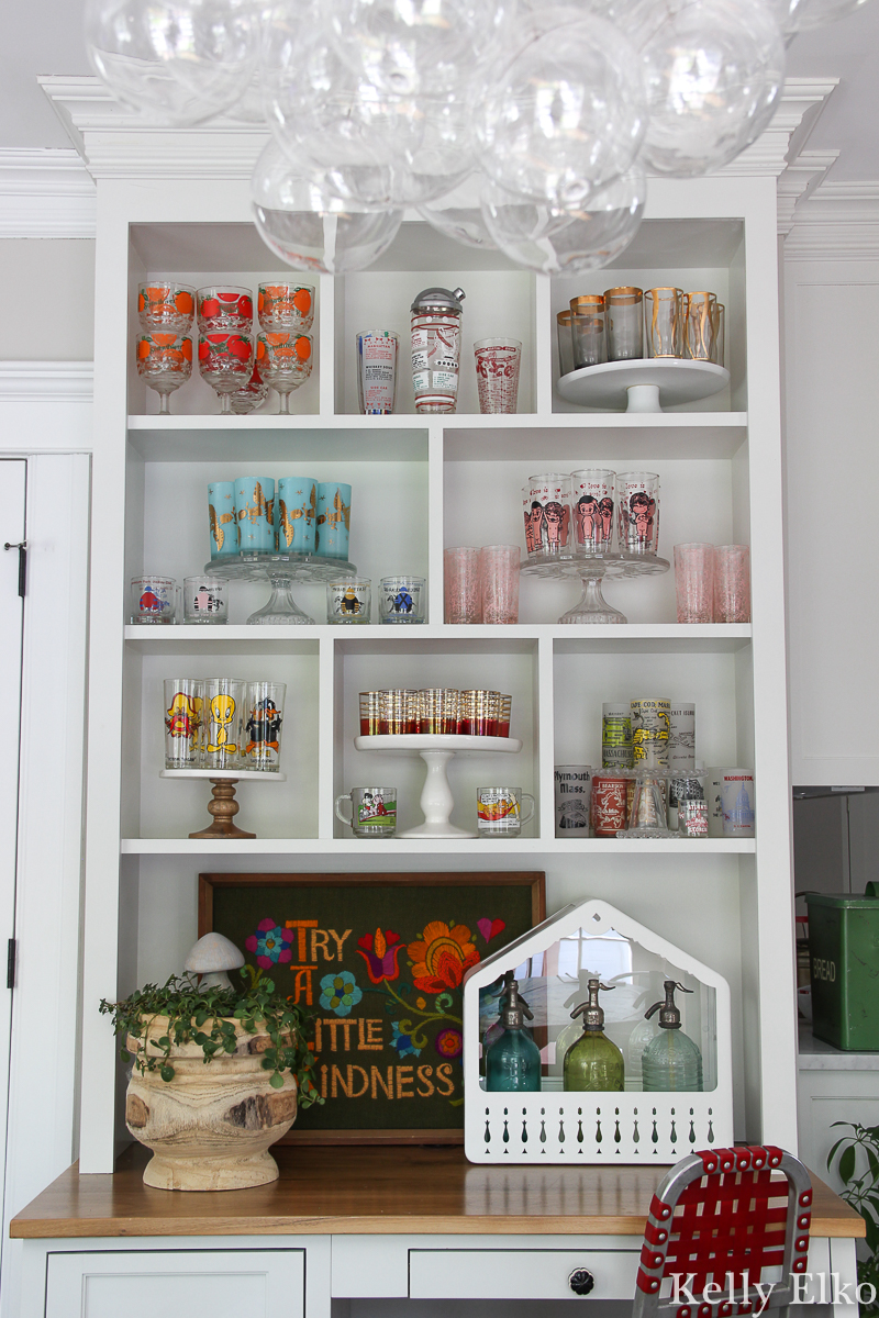 Love this colorful vintage drinking glass display in this white kitchen kellyelko.com #vintageglass #vintageglasses #drinkingglasses #vintagedrinkingglass #collectibles #collections #collect #collector #kitchendecor #vintagedecor #colorfuldecor #thrifted #vintagemodern #shelfie #kellyelko #kitchen