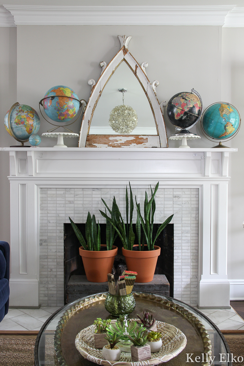 Love this living room with vintage globe collection the mantel and that architectural piece turned mirror kellyelko.com #mantel #manteldecor #eclecticdecor #vintagedecor #globes #vintageglobes #bohodecor #plants #houseplants #fireplacedecor #vintagemodern #interiordecor #kellyelko