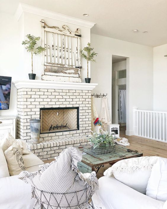 Love this antique architectural find on the mantel in this farmhouse kellyelko.com #mantel #farmhousemantel #manteldecor #farmhouse #farmhousedecor #farmhousemantel #upcycle #repurpose #architecturalelement #brickfireplace #whitebrick #farmhousefamilyroom #fixerupper