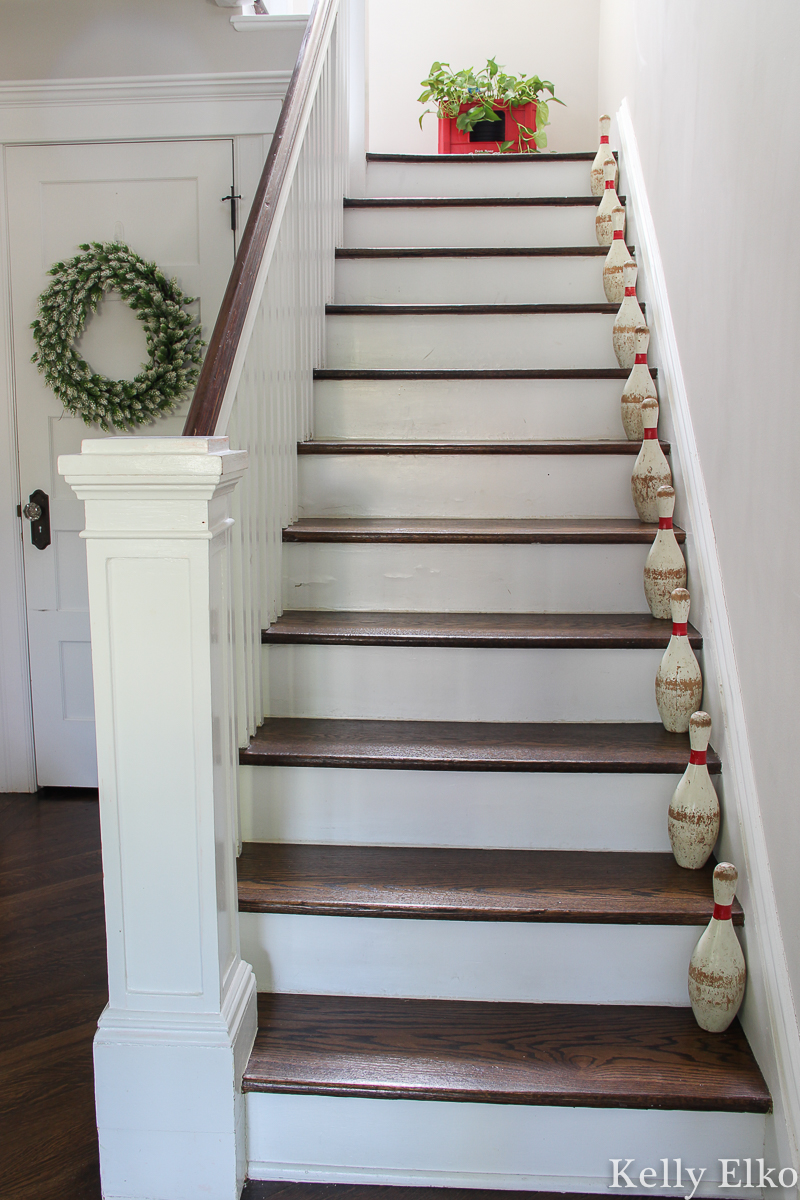 Love the vintage lawn bowling pin set on the staircase of this farmhouse foyer kellyelko.com #vintage #vintagedecor #bowlingpins #farmhouse #farmhousedecor #farmhouseentry #foyer #foyerdecor #staircasedecor #graypaint #neutraldecor #summerdecor #eclecticdecor #collections #collector #thrifted #houseplants #plantlady