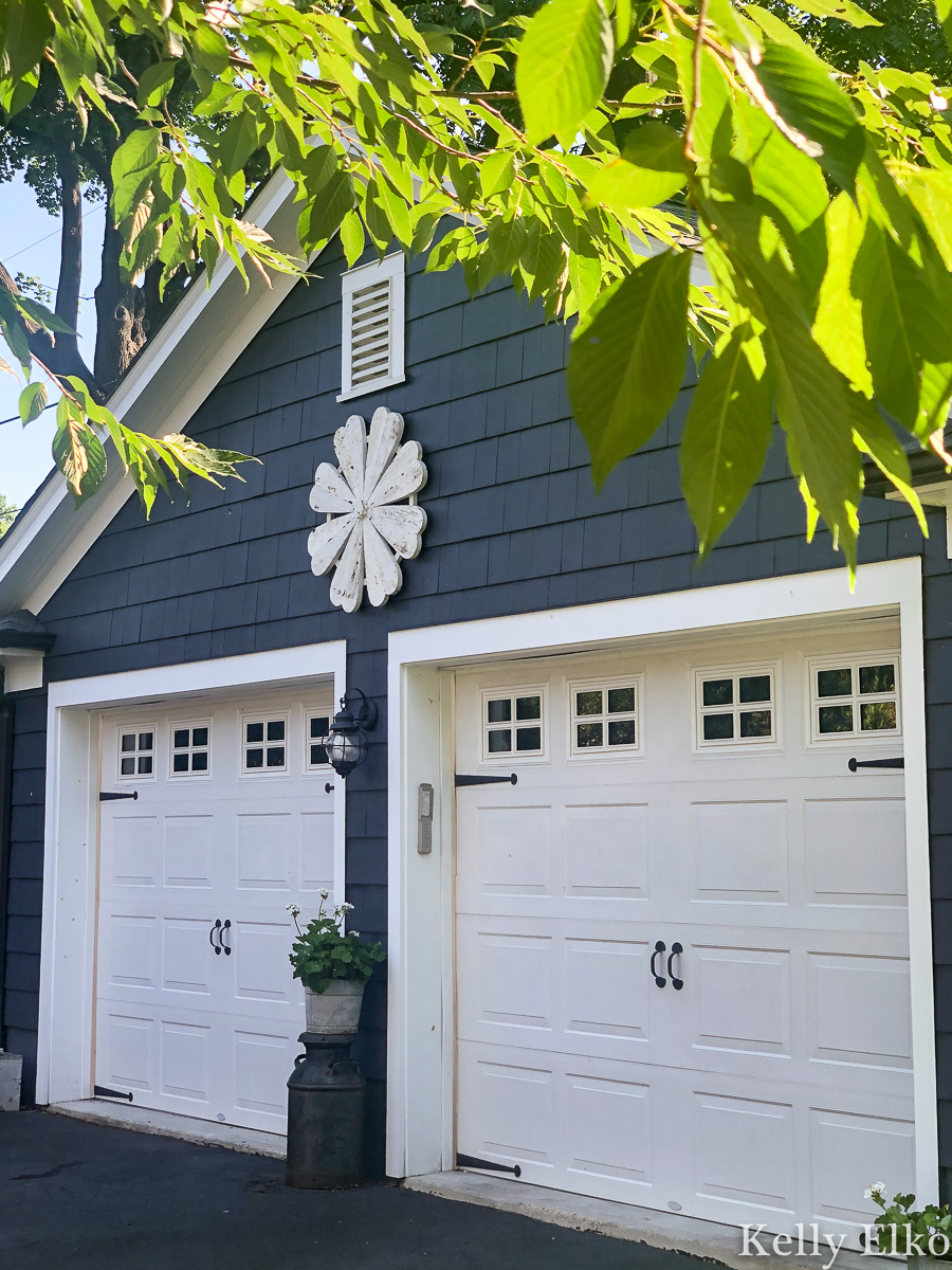 Love this giant barn wood flower hung on the garage for instant curb appeal kellyelko.com #garage #outdoordecor #farmhousedecor #farmhousestyle #whiteflower #curbappeal #halenavy #bluepaint #paintcolors #exteriorpaintcolors #garagedoors