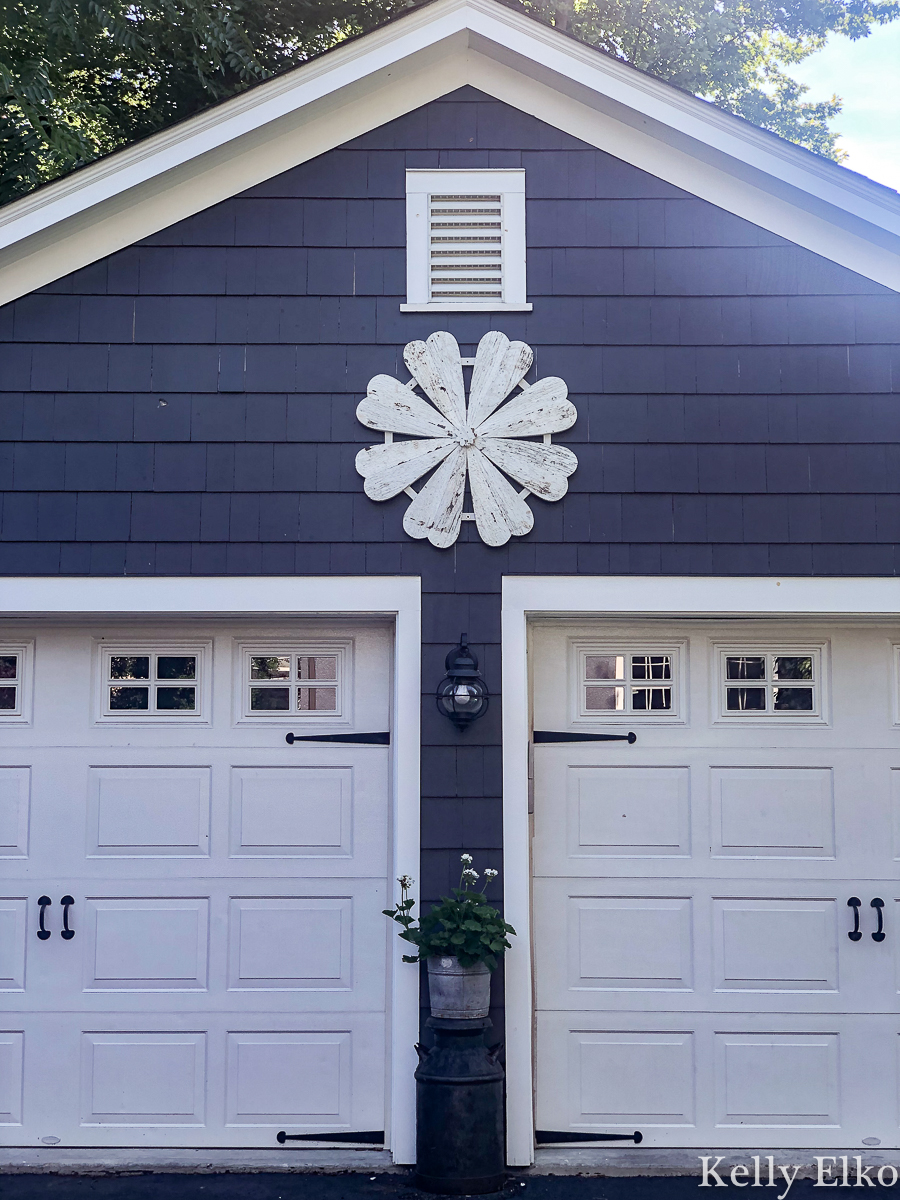 Love this giant barn wood flower hung on the garage for instant curb appeal kellyelko.com #garage #outdoordecor #farmhousedecor #farmhousestyle #whiteflower #curbappeal #halenavy #bluepaint #paintcolors #exteriorpaintcolors