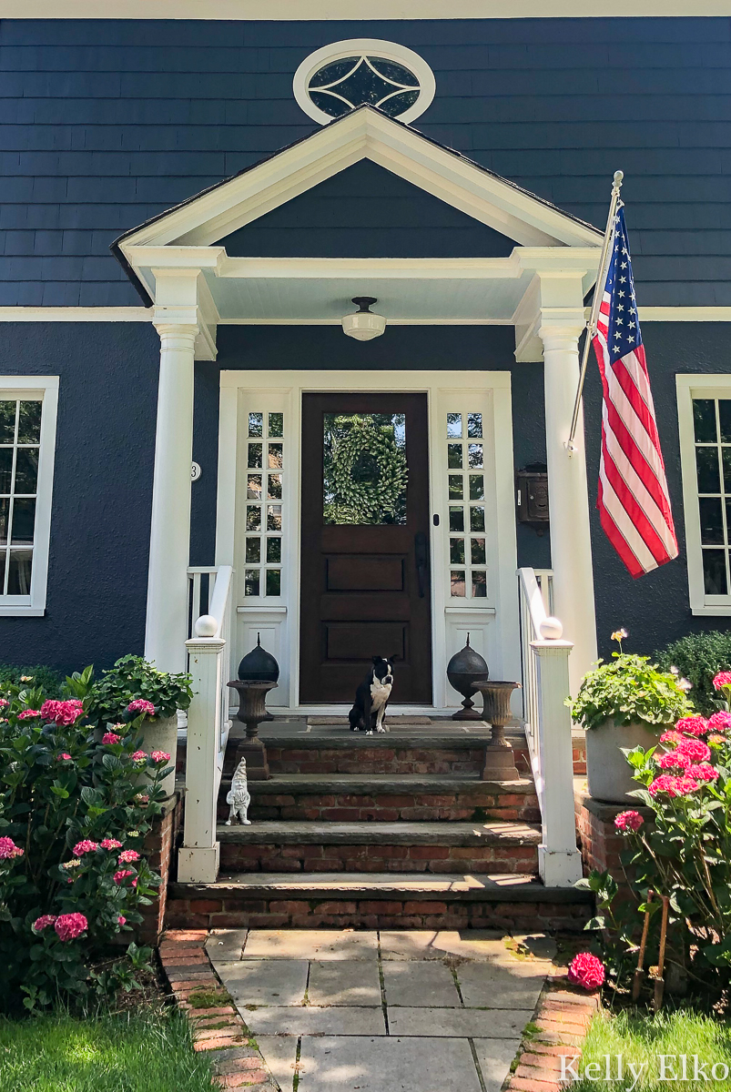 Love this bold blue house and charming small front porch kellyelko.com #blue #bluepaint #bluehouse #halenavy #housepaint #housecolors #curbappeal #oldhouse #oldhome #oldhouses #fixerupper #frontporch #landscaping #gardening #gardens #dormers #farmhouse #farmhousedecor #flag #americanflag #hydrangeas #porchdecor