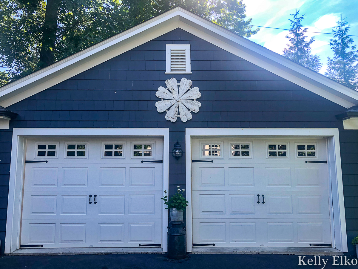 Love this giant barn wood flower hung on the garage for instant curb appeal kellyelko.com #garage #outdoordecor #farmhousedecor #farmhousestyle #whiteflower #curbappeal #halenavy #bluepaint #paintcolors #exteriorpaintcolors #detachedgarage