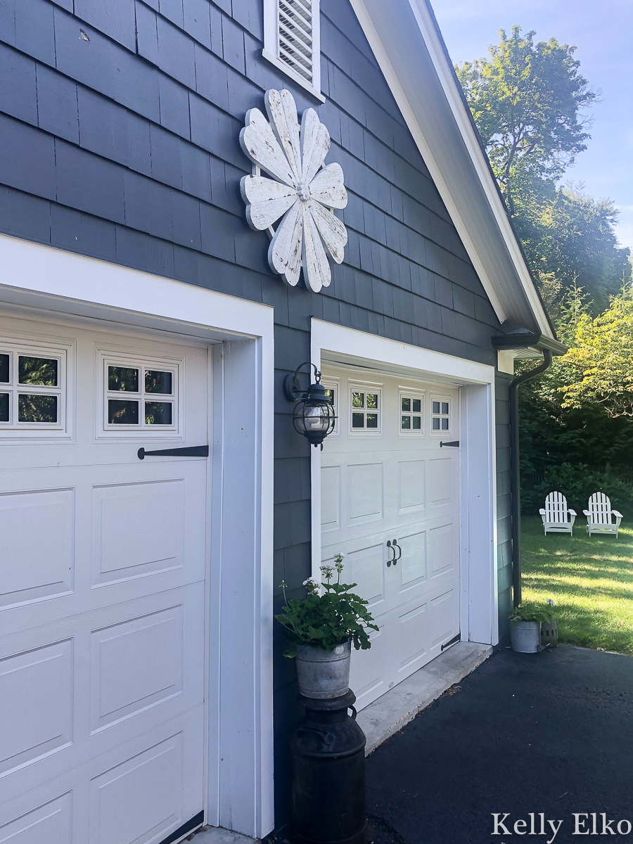 Love this huge barn wood flower that adds so much curb appeal to this garage kellyelko.com #barnwood #farmhouse #farmhousedecor #farmhousestyle #garage #halenavy #bluehouse #bluepaint #curbappeal #whiteflower #outdoordecor