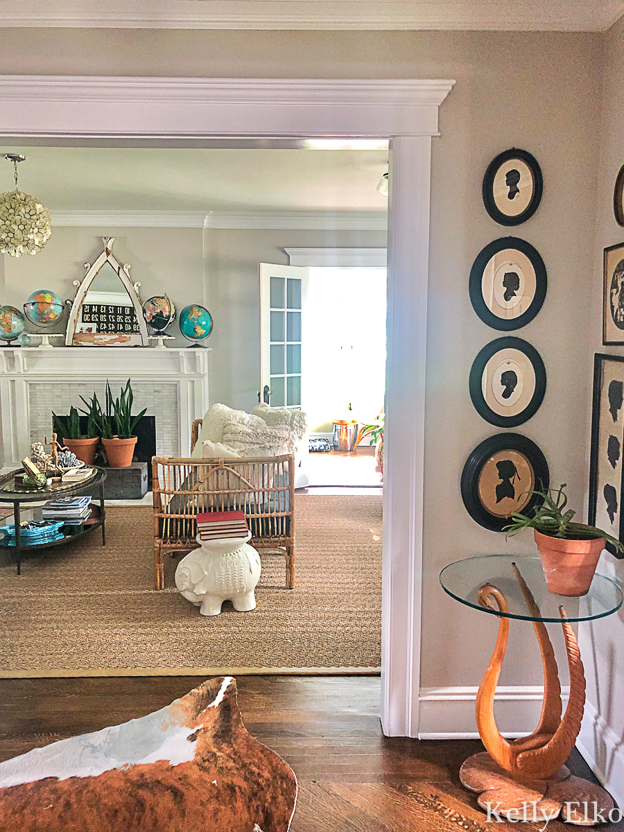 Love this eclectic living room with so many unique vintage finds kellyelko.com #vintagedecor #vintagefurniture #eclecticdecor #livingroomdecor #globes #rattan #collections