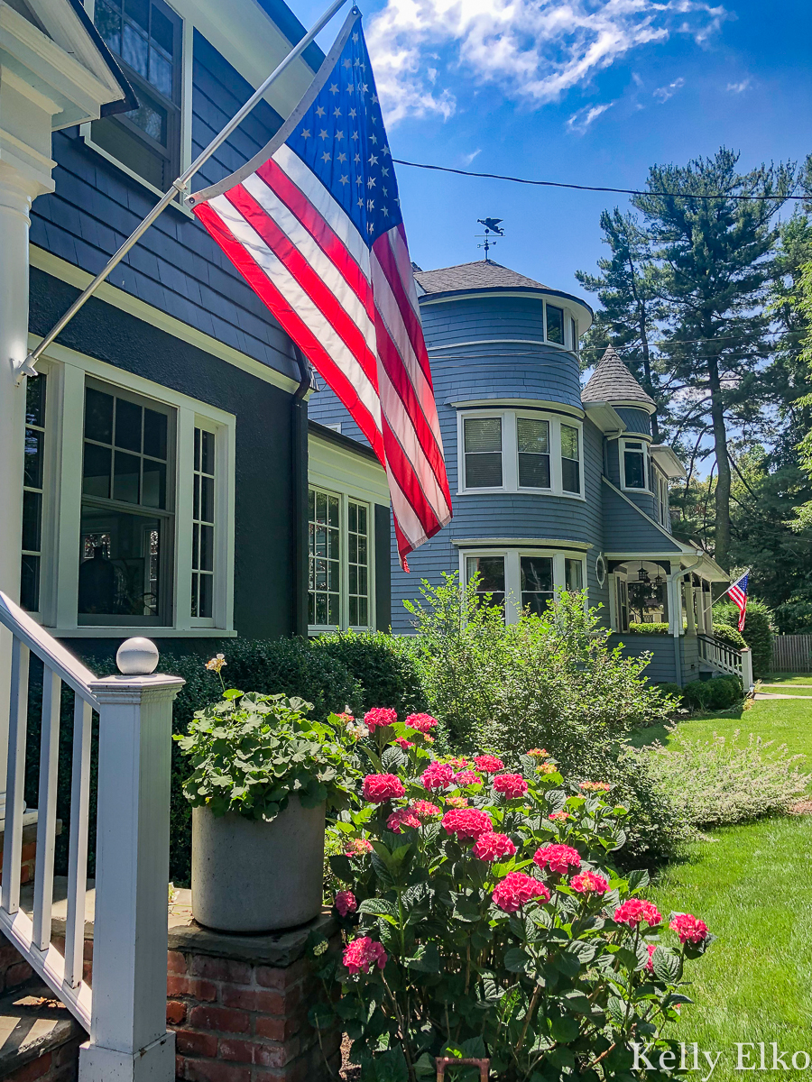 Love an American flag hung on a house kellyelko.com #blue #bluepaint #bluehouse #halenavy #housepaint #housecolors #curbappeal #oldhouse #oldhome #oldhouses #fixerupper #frontporch #landscaping #gardening #gardens #dormers #farmhouse #farmhousedecor