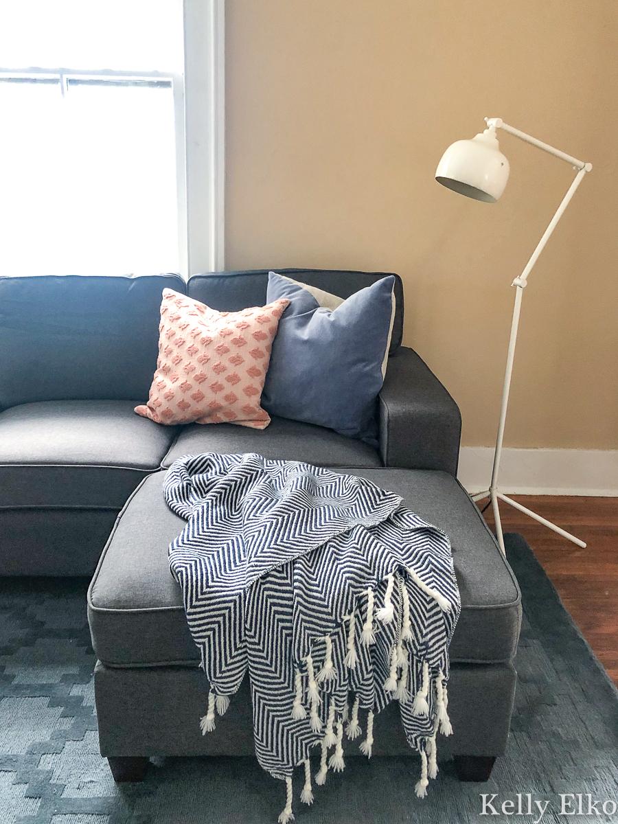 Beautiful sofa with cozy throw and pillows kellyelko.com #cozydecor #throwblanket #floorlamp #sectionalsofa #collegedecor #apartmentdecor