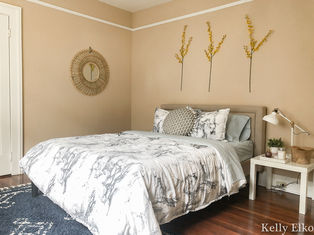 How to furnish a college apartment on a budget - love the idea of hanging flowering branches on the wall kellyelko.com #bedroom #bedroomdecor #floralart #apartmentdecor #apartmentfurniture #inexpensivedecor #budgetdecor #budgetart #platformbed #eclecticbedroom #thriftydecorideas