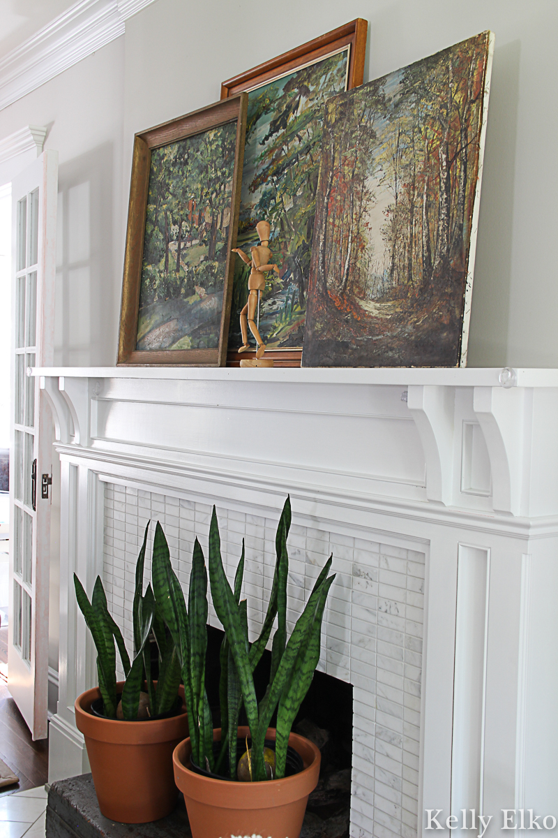 Love this fall mantel with a trio of vintage landscape paintings and snake plants covering the fireplace opening kellyelko.com #vintagedecor #vintagepaintings #vintageart #vintagelandscape #falldecor #fallmantel #houseplants #manteldecor #fallhometour
