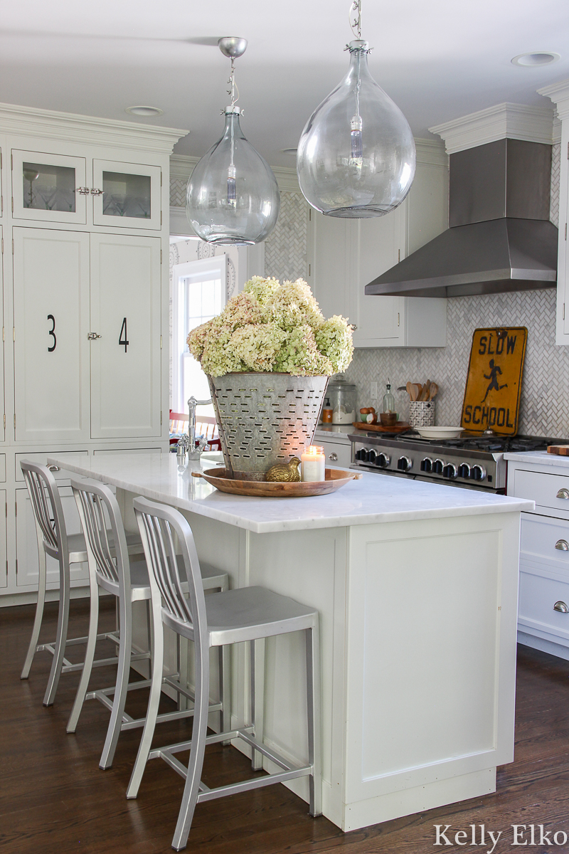 White kitchen with beautiful glass pendant lights and marble counters and backsplash kellyelko.com #whitekitchen #kitchen #farmhousekitchen #whitecabinets #farmhousedecor #kitchendecor #fallkitchen #hydrangeas