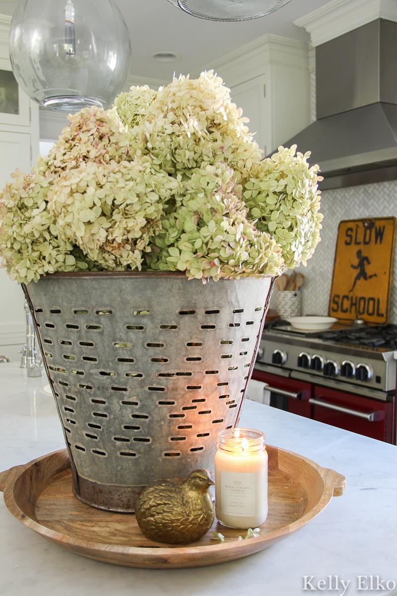 Love this huge zinc bucket filled with dried hydrangeas for fall kellyelko.com #hydrangeas #driedhydrangeas #driedflowers #falldecor #vintagedecor #vintagefall #fallkitchen #whitekitchen #eclecticdecor