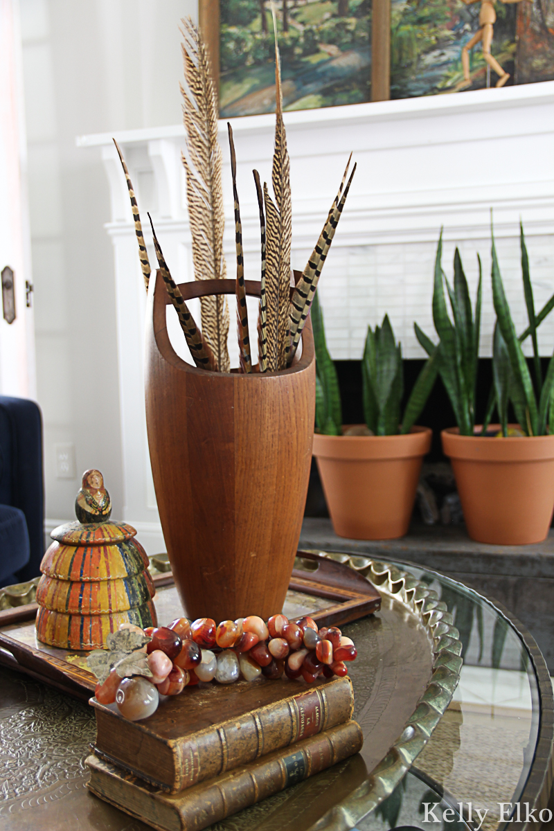 Love these feathers displayed in a vintage teak ice bucket - so many beautiful fall decorating ideas kellyelko.com #fall #falldecor #vintagedecor #vintage #fallhometour #feathers #eclecticdecor #collections