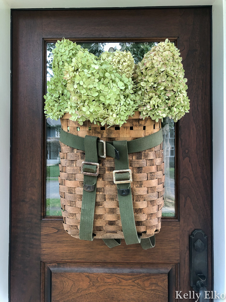Love this vintage Adirondack basket used as a door wreath kellyelko.com #basket #basketwreath #wreath #wreaths #fallwreath #summerwreath #curbappeal #diywreath #hydrangeas #limelight #vintagedecor #eclecticdecor #frontdoor