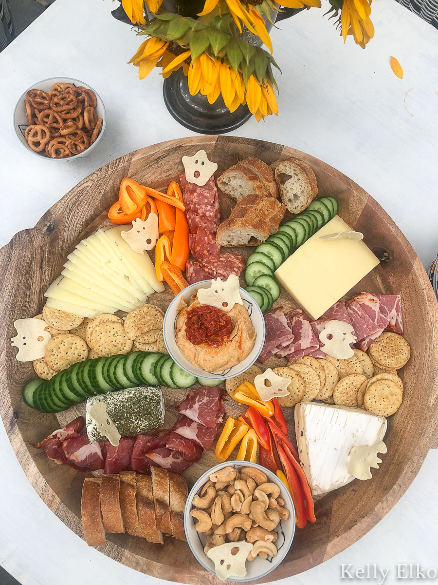 This fall charcuterie board is huge! I love the little ghost shaped crackers kellyelko.com #charcuterie #charcuterieboard #cheeseplatter #cheeseboard #meatandcheese #appetizers #partyfood #boards #fallfood #fallparty #fallcharcuterie #partyfood