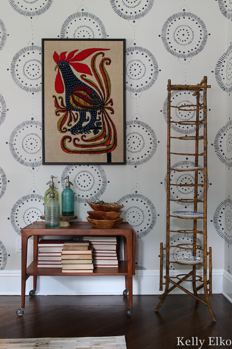Love this eclectic mix of vintage pieces including a Danish modern bar cart, antique bamboo plate rack and unique crewel rooster art kellyelko.com #vintage #vintagedecor #antique #antiquedecor #eclecticdecor #danishmodern #bamboo #diningroomdecor #crewelwork #vintageart #vintagebamboo