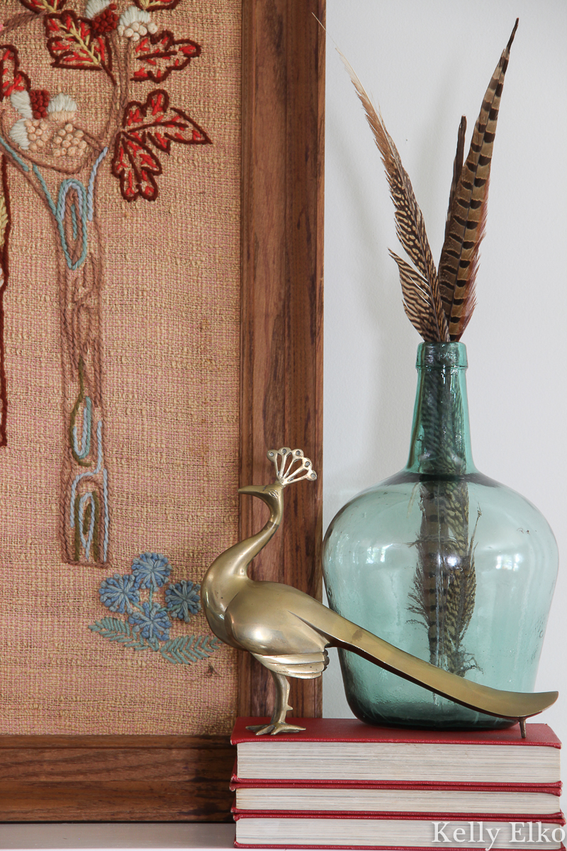 Vintage mantel with brass peacock, crewel art and feathers in glass kellyelko.com #vintagedecor #falldecor #fallmantel #brass #vintagebrass #peacock #eclecticdecor