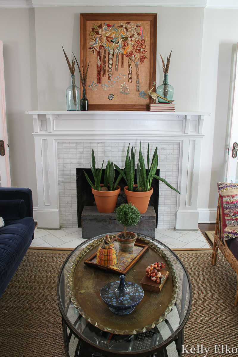 Love this eclectic living room with vintage crewel art and other unique pieces kellyelko.com #fall #falldecor #eclecticdecor #uniquedecor #livingroom #livingroomdecor #fallmantel #manteldecor #vintageart #crewel #houseplants #hearth