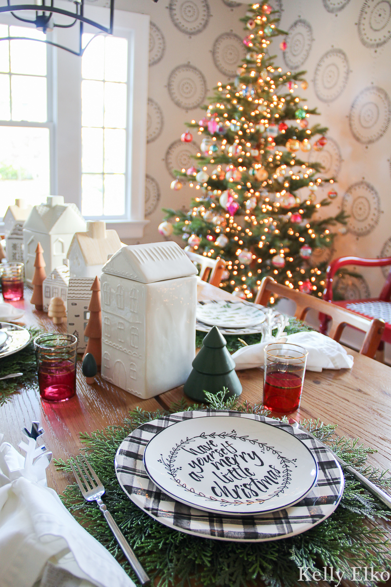 Love this festive Christmas table setting with plaid plates and cedar placemats and the cute little ceramic house centerpiece kellyelko.com #christmasdecor #christmastable #christmasplates #christmascenterpiece #christmasdiningroom #farmhousechristmas #christmastree #vintagechristmas