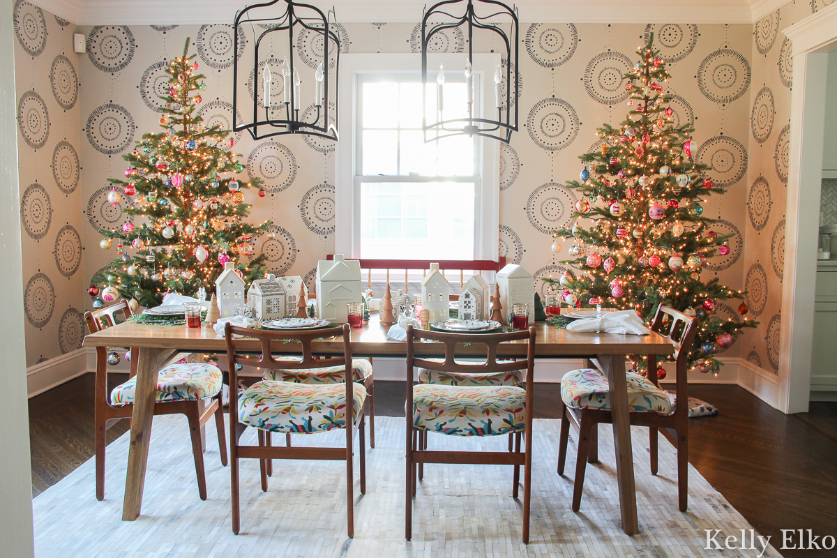 Love this beautiful Christmas dining room with a pair of realistic Christmas trees against a wall mural kellyelko.com #wallmural #christmasdiningroom #christmasdecor #vintagechristmas #farmhousechristmas #eclecticchristmas #sparsechristamstrees #realisticchristmastrees #danishmodern #MCMfurniture #colorfulchristmas