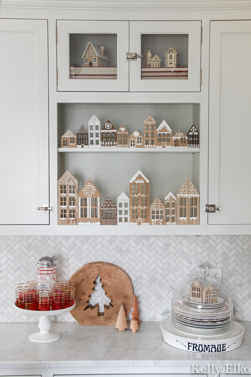How cute is this DIY Wood Gingerbread House village in this farmhouse kitchen kellyelko.com #christmas #christmascrafts #christmasdecor #diychristmas #diychristmasdecor #gingerbreadhouse #kidscrafts #christmaskitchen #whitekitchen