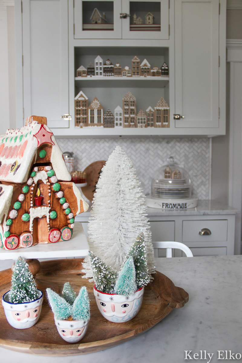 Beautiful Christmas kitchen with vintage gingerbread house cookie jar and a Diy wood cookie jar village kellyelko.com #vintagechristmas #christmaskitchen #retrochristmas #gingerbreadhouse #santa #santadecor #farmhousechristmas #diychristmas #bottlebrushtrees #christmashometour