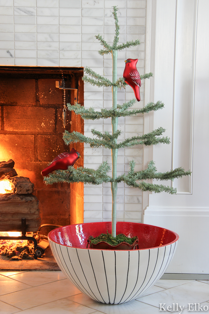 Love this little feather tree in a big red bowl kellyelko.com #feathertree #sparsetree #sparsechristmastree #vintagechristmas #retrochristmas #cardinalornament #christmasmantel