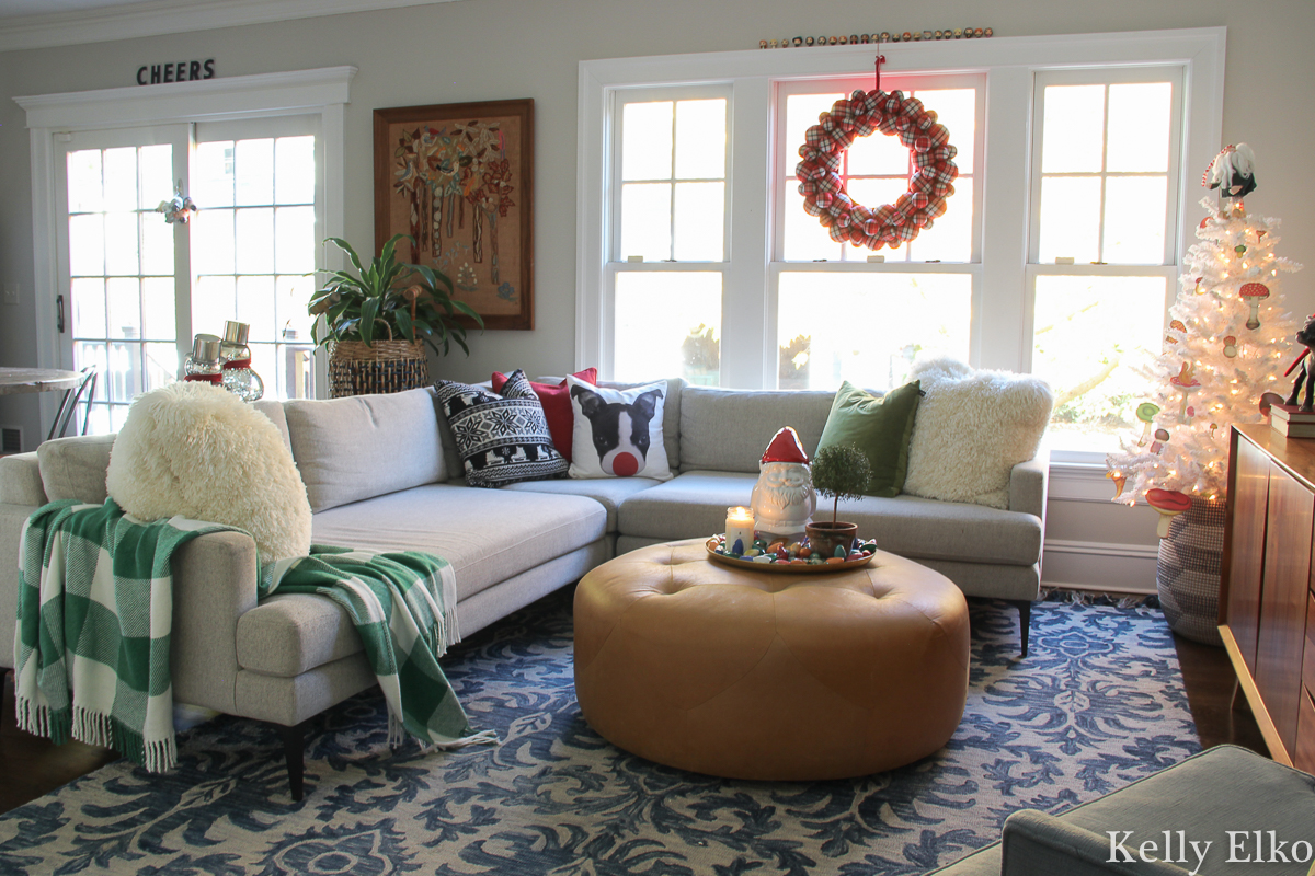 Festive Christmas decor and I love the dog Rudolph pillow! kellyelko.com #christmasdecor #christmasfamilyroom #christmaswreath #colorfulchristmas #whitechristmastree #plaidthrow #christmaspillows #sectionalsofa #loloirug