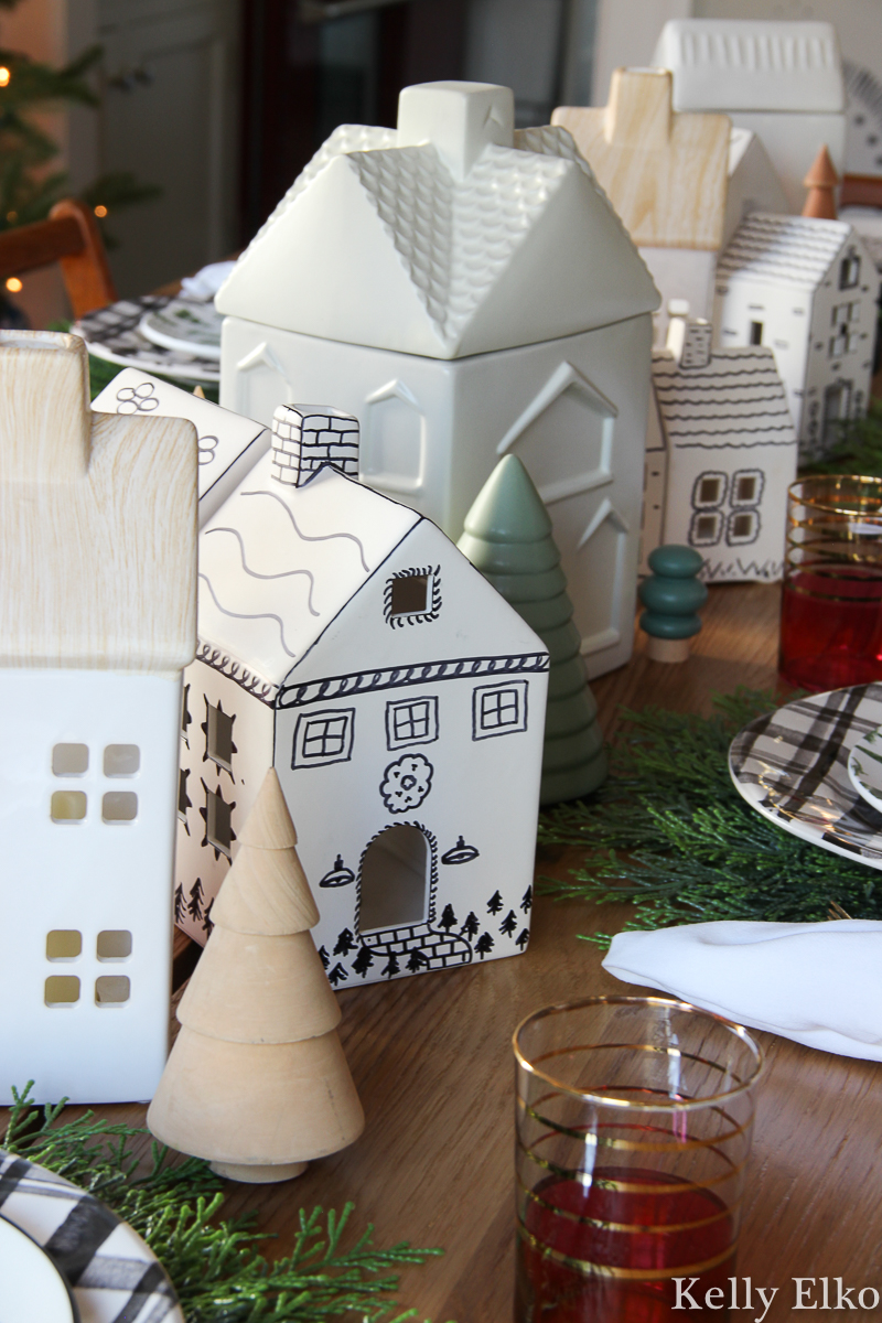 Love this Christmas centerpiece of little white ceramic houses and wood trees kellyelko.com #christmasdecor #christmastable #christmascenterpiece #ceramichouses #farmhousechristmas #vintagechristmas #diychristmas #christmascrafts #littlechristmashouses