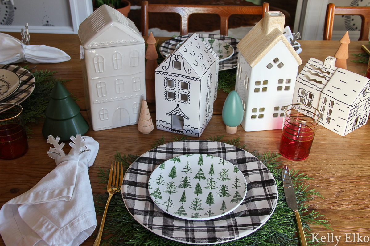 Love this little white ceramic Christmas houses centerpiece and the plaid plates with cute tree plates on top kellyelko.com #christmastable #christmascenterpiece #christmasplates #ceramichouses #whitechristmashouses #ceramicchristmashouses #diychristmasdecor #christmasplacesetting #farmhosuechristmas