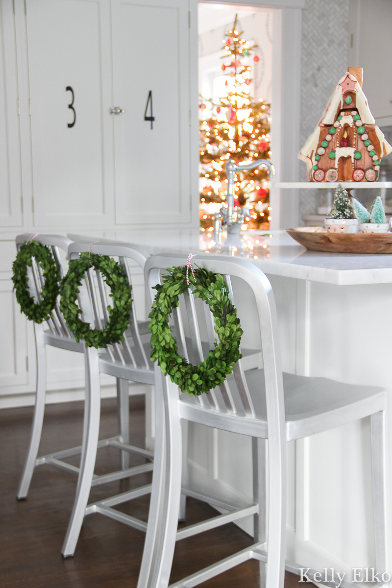 Love the preserved boxwood wreaths on the barstools in this beautiful Christmas kitchen kellyelko.com #christmas #christmasdecor #christmaskitchen #christmaswreath #boxwoodwreath #vintagechristmas #retrochristmas #farmhousechristmas #gingerbreadhouse #vintagedecor #whitekitchen