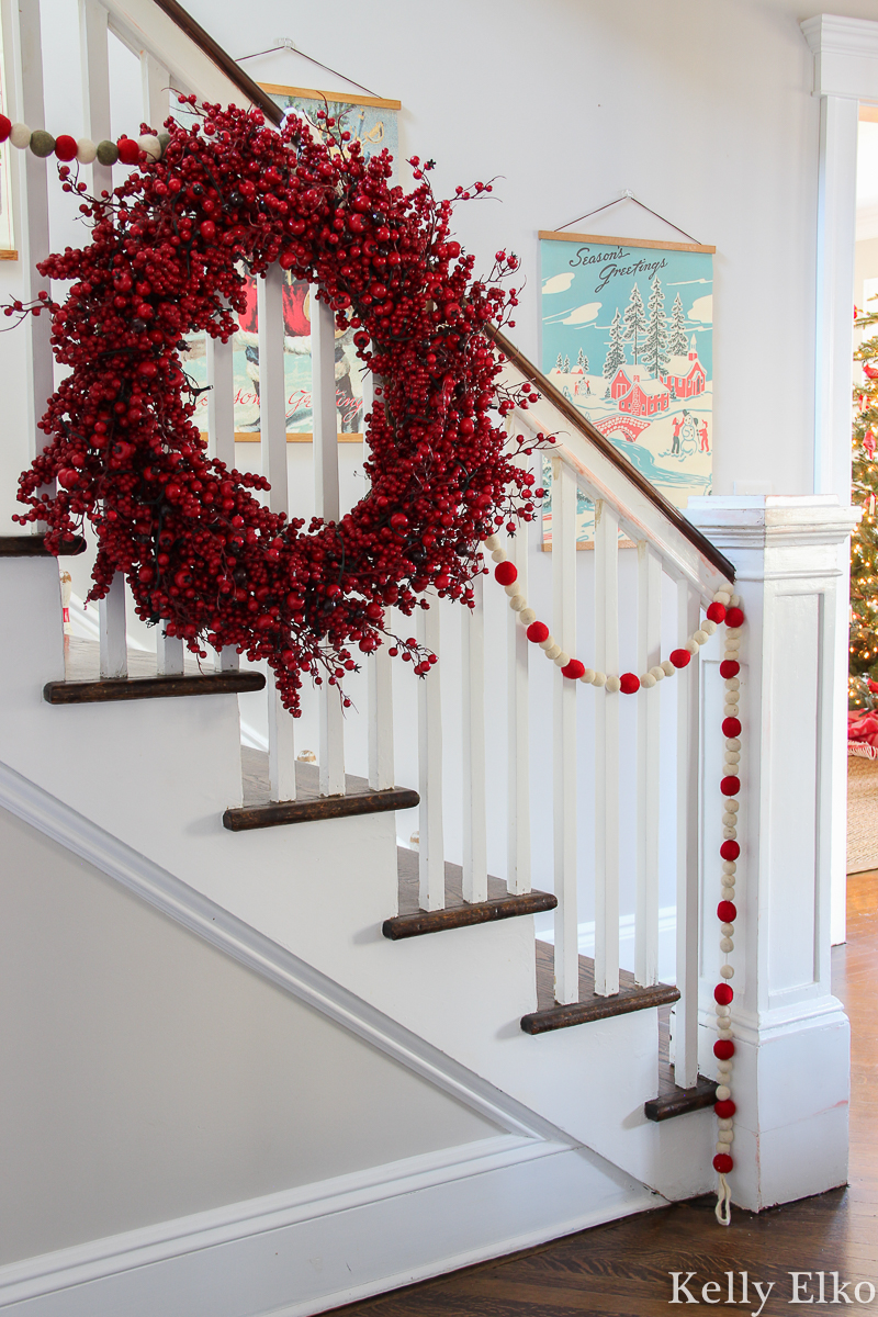 Love this retro Christmas art on the staircase wall in this beautiful home kellyelko.com #christmasart #vintageart #retroart #christmasfoyer #christmasentry #vintagechristmasart #retrochristmasart #vintagedecor #foyerdecor #entrydecor #berrywreath #christmasbannister #christmasgarland #farmhousechristmas