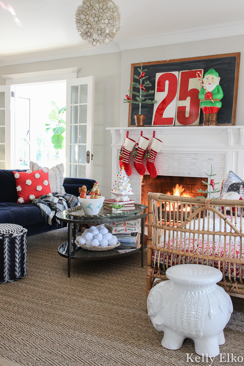 Love this colorful living room and the retro Christmas mantel with cute elf blow mold and pom pom stockings kellyelko.com #christmashouse #christmashometour #christmasmantel #retrochristmas #vintagechristmas #livingroomdecor #rattanfurniture #christmasstockings #blowmold #christmaslivingroom