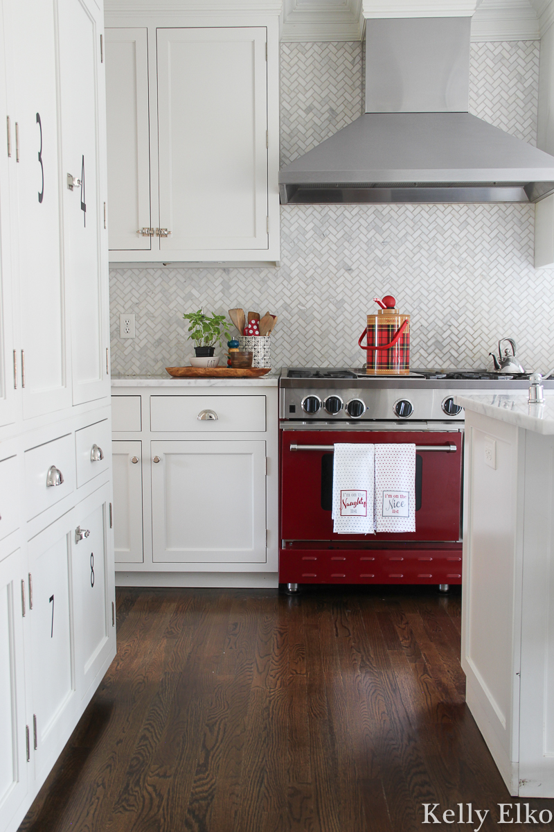 Beautiful red stove is the perfect pop of color in this classic white kitchen kellyelko.com #whitekitchen #redstove #christmaskitchen #vintagechristmas #carraramarble