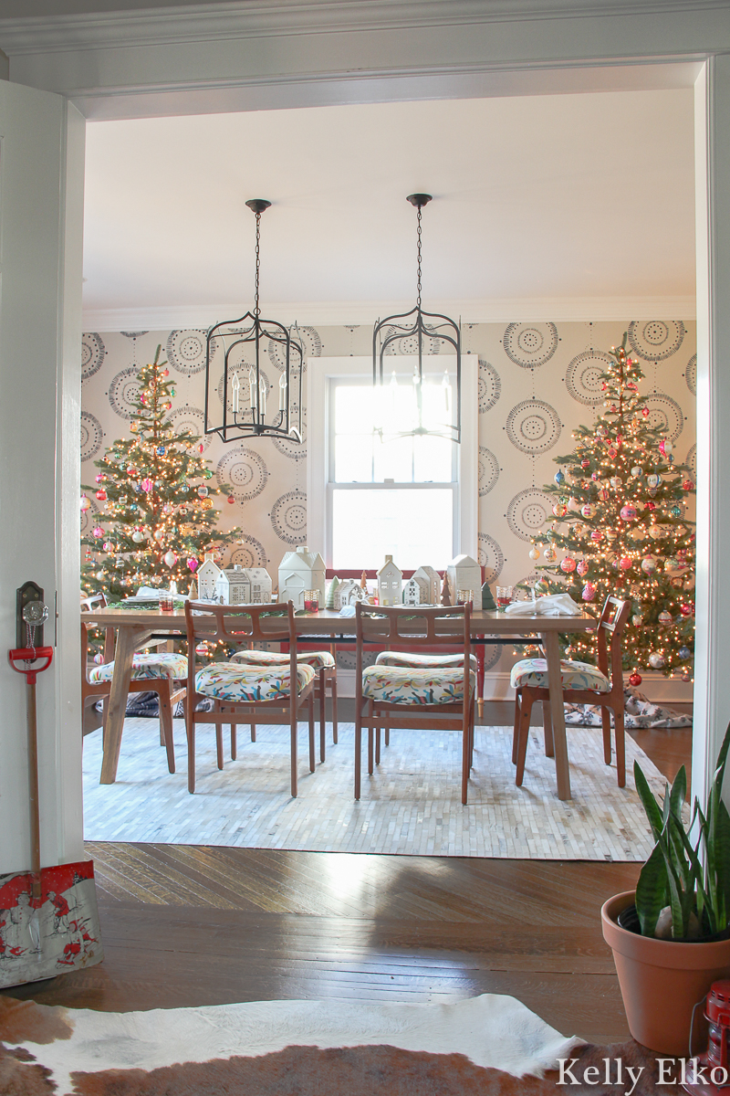 Love the pair of sparse Christmas trees in this stunning dining room kellyelko.com #christmasdecor #christmastrees #realisticchristmastree #sparsechristmastree #christmasdiningroom #farmhousechristmas