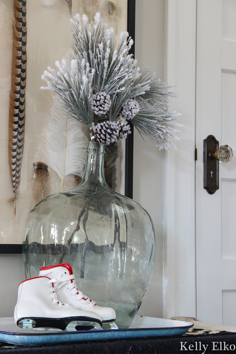 Love this simple sprig of greenery in a big glass jar kellyelko.com #christmasdecor #farmhousechristmas #iceskates #vintagechristmas