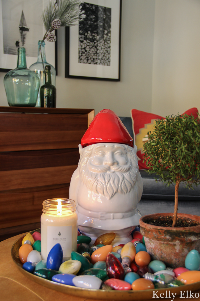Love this little gnome cookie jar surrounded by vintage Christmas lightbulbs kellyelko.com #christmasdecor #gnome #christmasgnome #vintagechristmas #vintagechristmaslights #retrochristmas #christmashometour #colorfulchristmas