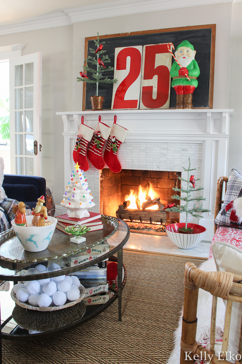 Love this vintage Christmas mantel with elf blow mold and big metal 25 numbers kellyelko.com #christmas #christmasdecor #christmasdecorations #christmasdecoratingideas #christmasmantel #vintagechristmas #retrochristmas #farmhousechristmas #christmasfireplace #christmaslivingroom #cozychristmas #holidayhousewalk #christmastrees #sparsechristmastree #feathertree #blowmold #christmasblowmold