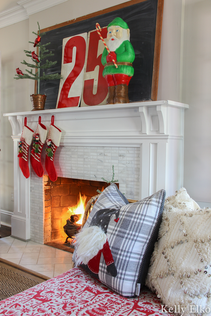 Love this retro Christmas mantel with elf blow mold and huge 25 numbers kellyelko.com #christmas #christmasdecor #christmasdecorations #retrochristmas #vintagechristmas #christmasmantel #christmasfireplace #farmhousechristmas #colorfulchristmas #christmasstockings #feathertree #gnome