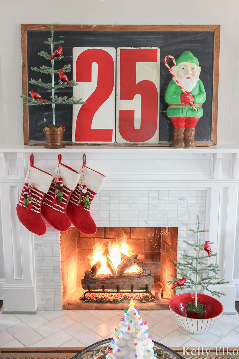 I love this fun retro Christmas mantel with the cutest elf blow mold and metal numbers kellyelko.com #christmas #christmashousetour #christmashouse #christmasmantel #christmasfireplace #vintagechristmas #retrochristmas #christmasstockings #feathertree #sparsechristmastree #cozychristmas #colorfulchristmas