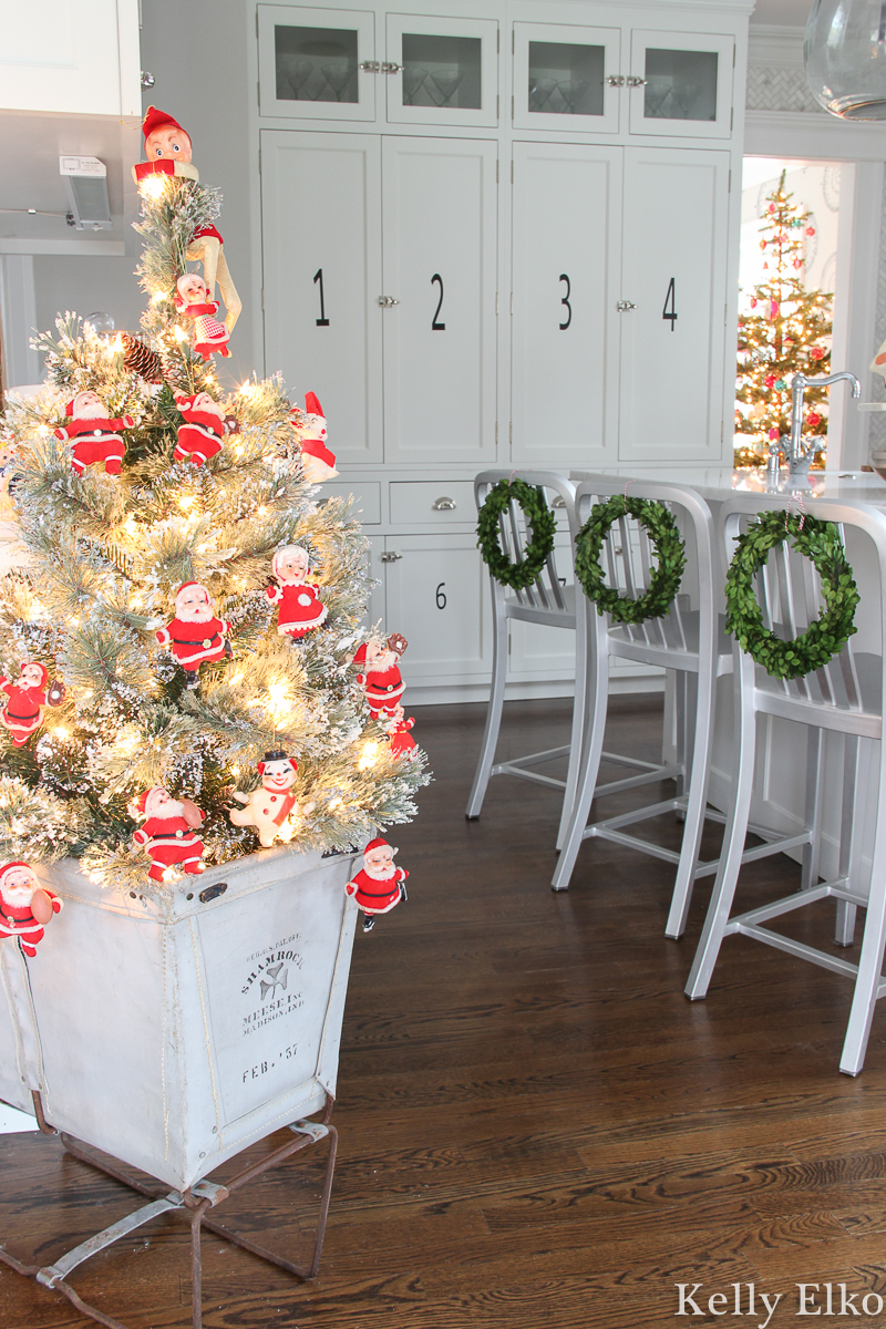 Love this festive Christmas home tour and the adorable little Christmas tree covered in vintage Santa ornaments in an old canvas laundry bin kellyelko.com #christmasdecor #christmasornaments #vintagechristmas #retrochristmas #vintagesanta #vintageornaments #vintagesantaornament #christmaskitchen #boxwoodwreaths #christmashometour #christmaswreath #vintagedecor