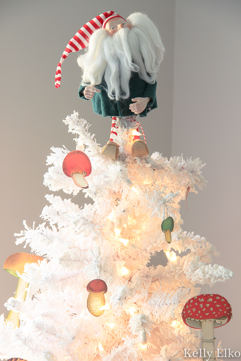 What a fun mushroom Christmas tree with DIY paper ornaments and a little elf tree topper kellyelko.com #christmastree #whitetree #whitechristmastree #paperornaments #diychristmas #mushrooms #mushroomornaments #elf #christmastree #christmasdecor #diychristmas #retrochristmas