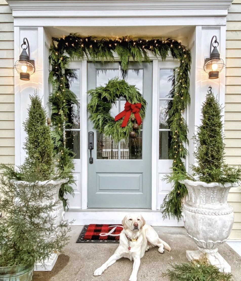 Favorite festive Christmas porches - love this classic fresh garland and wreath with big red bow #christmas #christmasporch #outdoorchristmasdecor #christmaswreath #christmasgarland #classicchristmas #farmhousechristmas