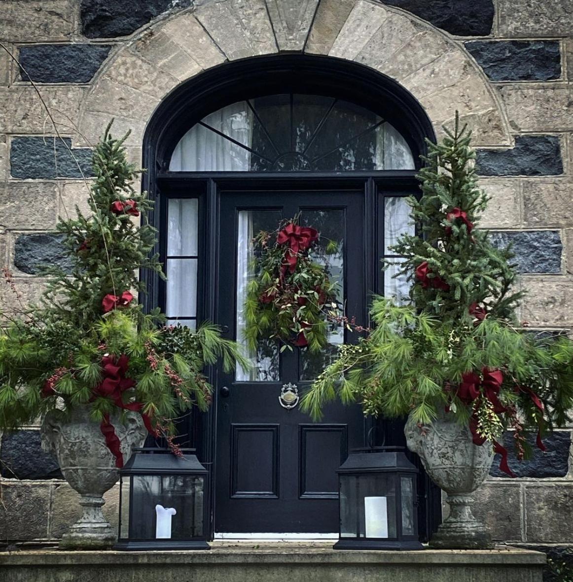 Beautiful old stone farmhouse dressed for Christmas #christmas #farmhousechristmas #christmasporch #christmasurns #christmasplanters #outdoorchristmasdecor #classicchristmas